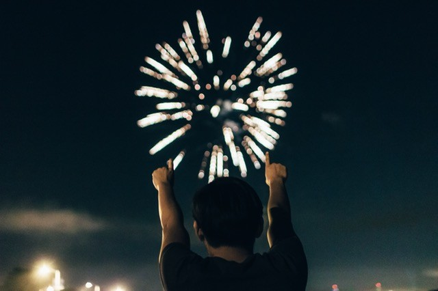 Man with both fingers up and fireworks