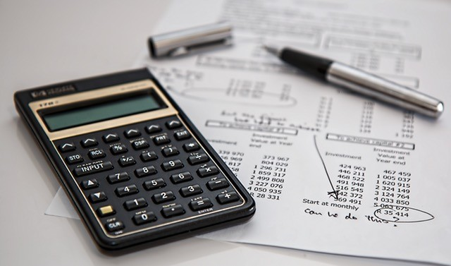 Calculator on piece of paper with ROI numbers.