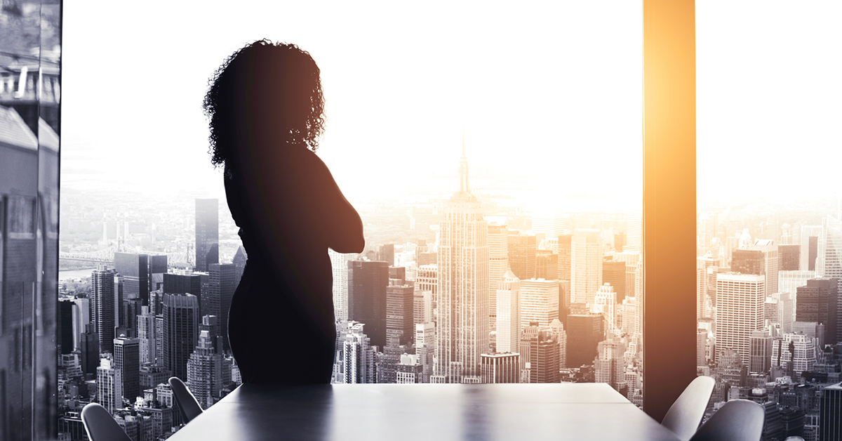 A loan officer contemplating financial services customer acquisition as she looks out a window at a city skyline.